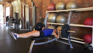 Picture of a female doing Bench Press Double Leg Drops Exercise