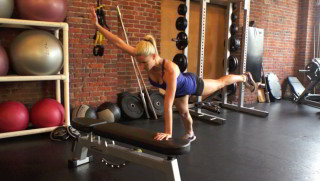 Picture of a female doing Four Point Superman on Bench Exercise