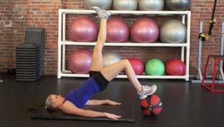 Picture of a female doing Single Leg Glute Bridge on Medicine Ball Exercise