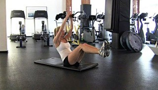 Picture of a female doing V-Sit Dumbbell Pass Exercise