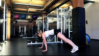 Picture of a female doing Walk-Out Knee Tuck Exercise