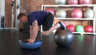 Picture of a male doing Bosu Push Up with Knee Tuck Exercise