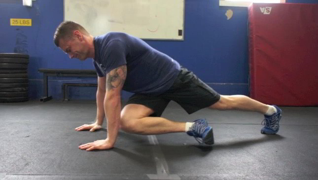Picture of a male doing Cross Under Knee Tucks Exercise