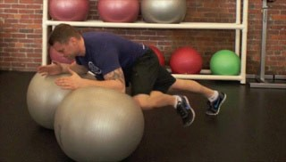 Picture of a male doing Double Stability Ball Knee-Ins Exercise