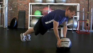 Picture of a male doing Medicine Ball Alternating Toe Taps Exercise