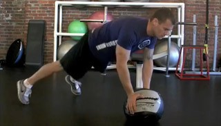 Picture of a male doing Medicine Ball Double Toe Taps Exercise