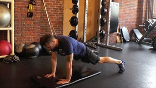 Picture of a male doing Push Up Plank Toe Taps Exercise