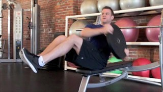 Picture of a male doing Weight Plate Trunk Twist on Bench Exercise